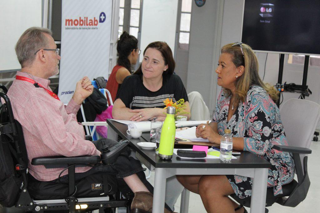 Foto de um homem cadeirante conversando com duas mulheres.