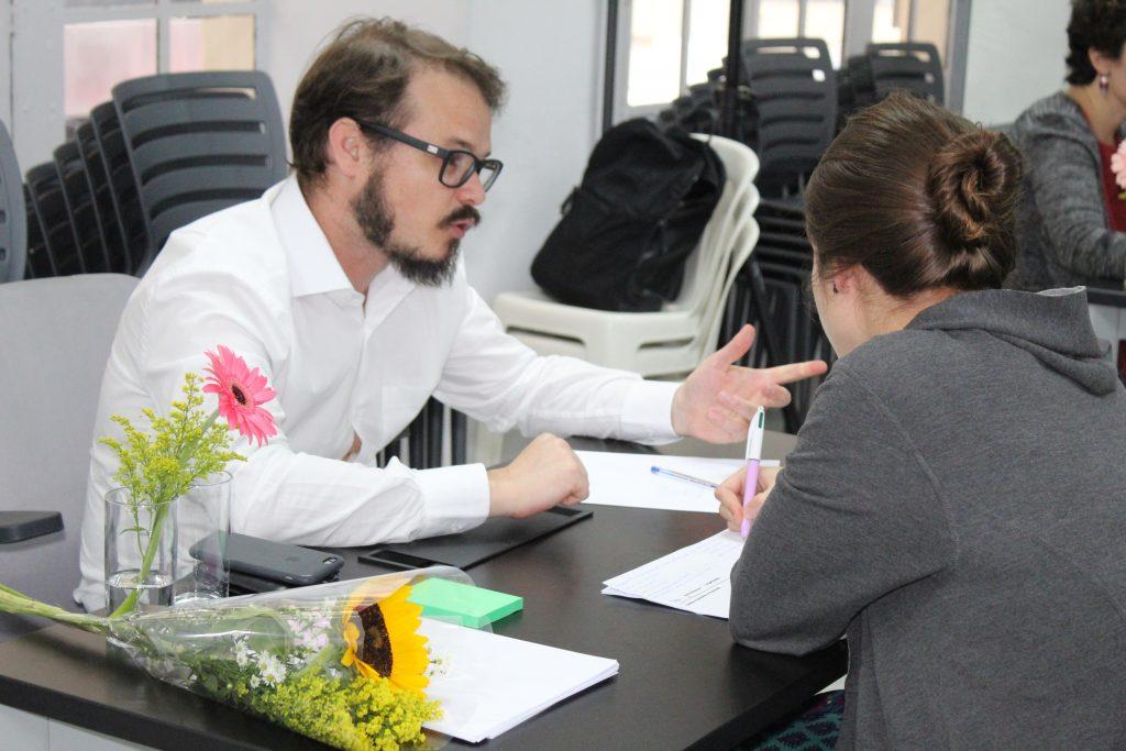 Foto de um homem branco de óculos e de barba conversa com uma mulher. Ela faz anotações em um papel.