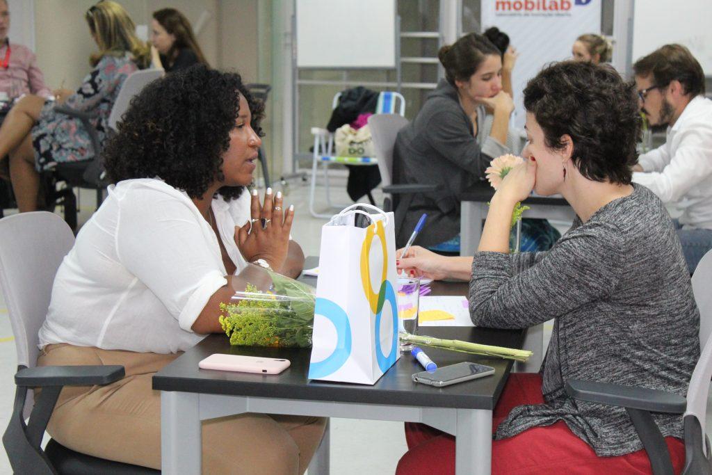 Foto de uma mulher negra sentada de frente para uma mulher branca.