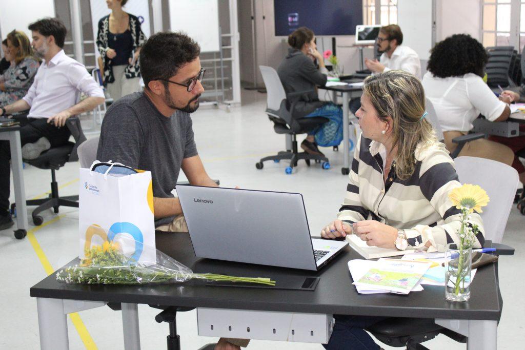 Foto de um homem branco de óculos e de barba sentado ao lado de uma mulher loira. Na frente dela, há um notebook.