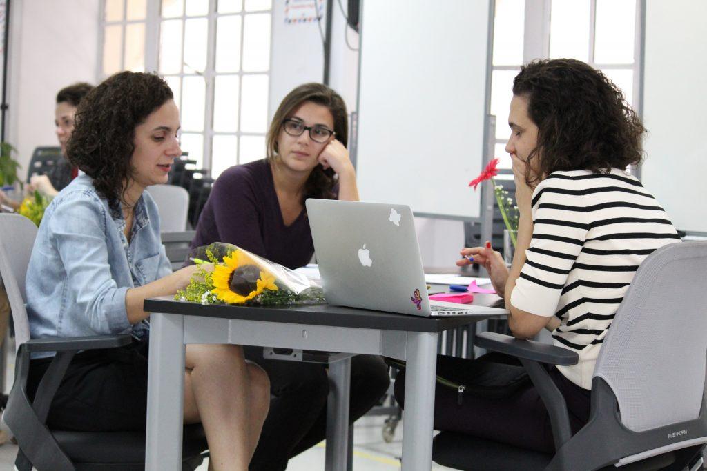 Foto de três mulheres conversando. Uma delas está com um notebook.