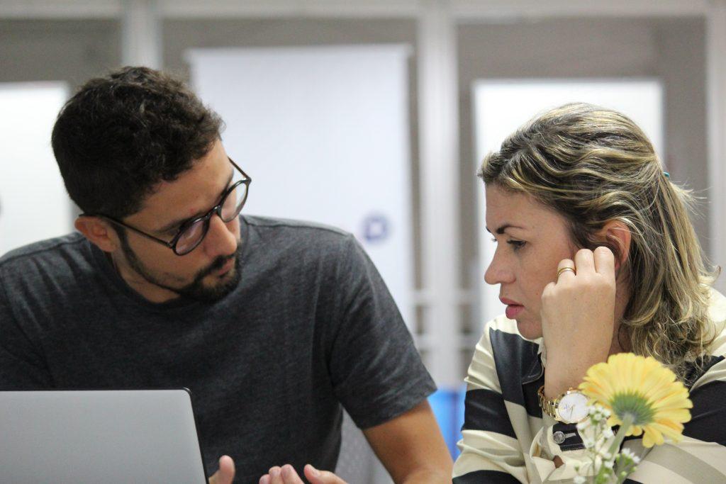Foto de um homem branco de óculos e de barba conversando com uma mulher loira.