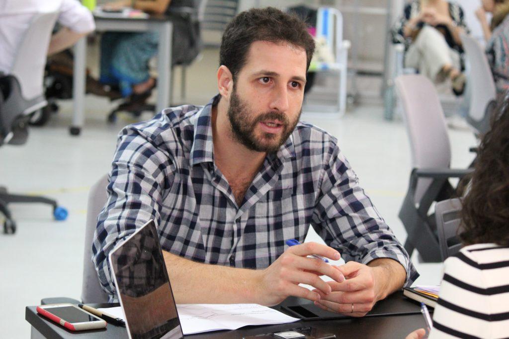 Foto de um homem branco de barba com os braços debruçados sobre uma mesa.