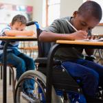 Foto de dois meninos sentados em uma sala de aula. Um deles é cadeirante.
