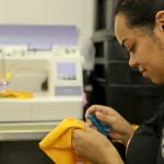 Foto do perfil de uma mulher com uma tesoura de desfazer costura em uma das mãos e na outra está um tecido amarelo. Ao fundo, há uma máquina de costura.