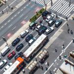 Foto aérea de uma avenida com carros, motos e ônibus parados. Há pedestres atravessando a faixa de segurança e outras pessoas nas calçadas e em um ponto de ônibus.